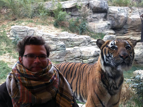 Gunner Maness, designer at Code & Color, sitting next to a Bengal tiger